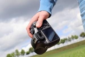 Eine Person hält eine Fotokamera in der Hand.