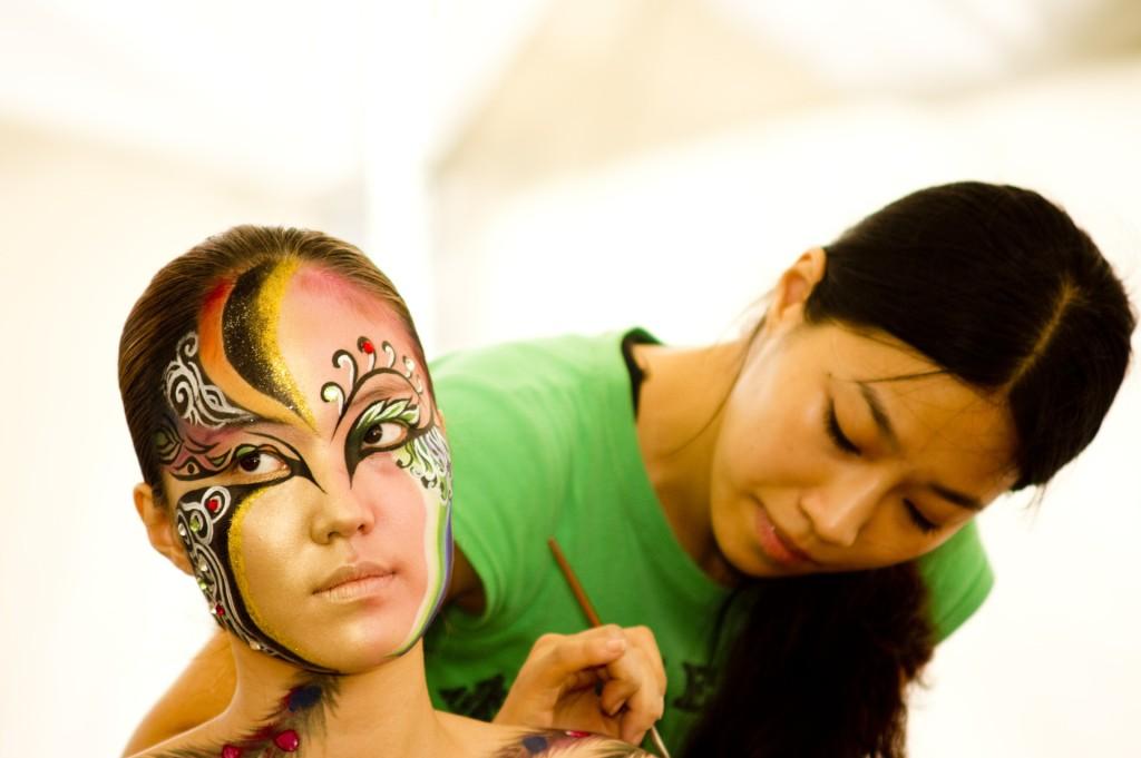 Eine Frau wird von einer Stylist geschminkt.