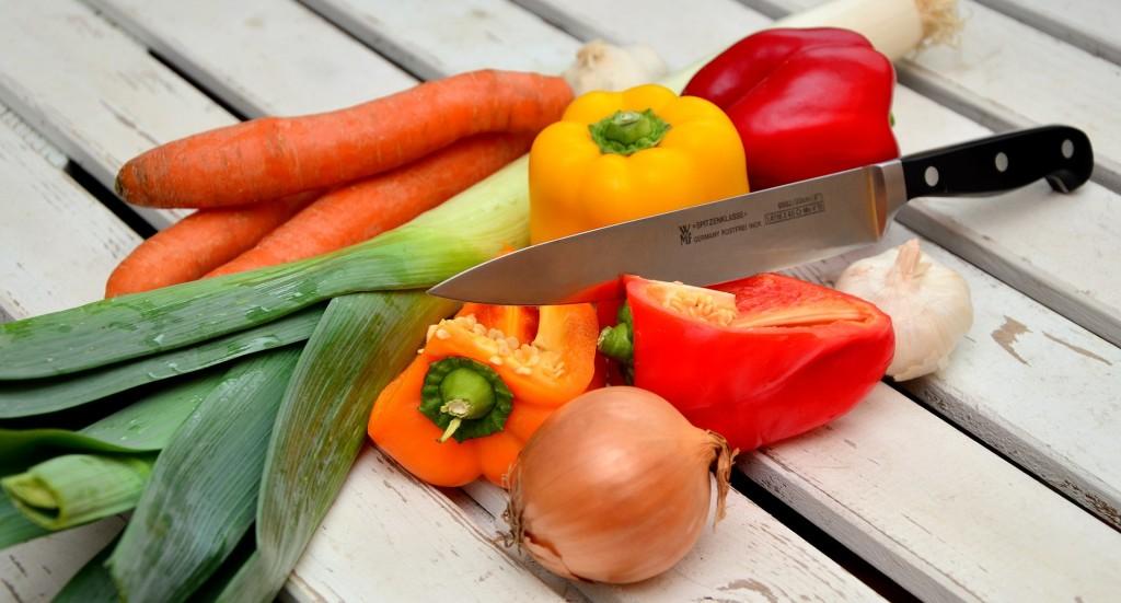Auf einem Tisch liegt Gemüse und ein Messer.