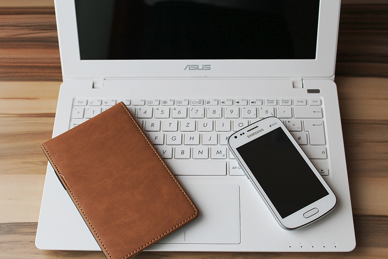 Smartphone, Laptop und ein Notizbuch