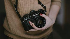 Eine Person hält eine Fotokamera