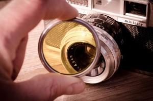 Eine Person hält eine gelbe Linse vor einer alten Kamera